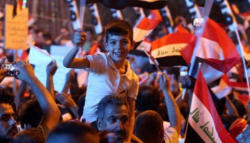 An-Iraqi-protester-carries-a-young-boy-o