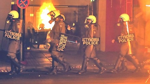 Download von www.picturedesk.com am 24.11.2016 (11:33).  Riot policemen walk closee to a burning rubbish bin after an annual protest march in Athens on November 17, 2009, to honour a 1973 anti-junta student revolt, ahead of protests set to mark a teenager's fatal shooting by police last year. Tens of thousands of demonstrators including students and adolescents marched through the city centre, chanting slogans against capitalism and NATO and in favour of migrants' legalisation. Around 6,500 officers were deployed across the capital for the annual march to the US embassy which is often marred by clashes between anarchists and riot police. AFP PHOTO/ LOUISA GOULIAMAKI - 20091117_PD4701 - Rechteinfo: Werbliche Nutzung nur nach Freigabe!