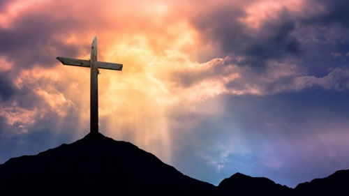 43936537 - silhouette of cross at sunrise or sunset with light rays