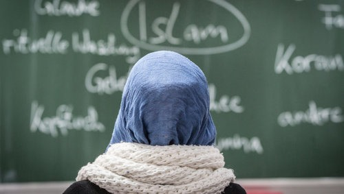 ABD0001_20160702 - ARCHIV - ILLUSTRATION - Eine junge Frau mit Kopftuch sitzt am 05.02.2015 in einer Schule in Frankfurt am Main (Hessen) bei einer Unterrichtsstunde zum Thema Islam. Foto: Frank Rumpenhorst/dpa (zu dpa ÇKopftuchverbot und Statistikstreit - Das Kreuz mit der LaizitŠtÈ vom 02.07.2016) +++(c) dpa - Bildfunk+++